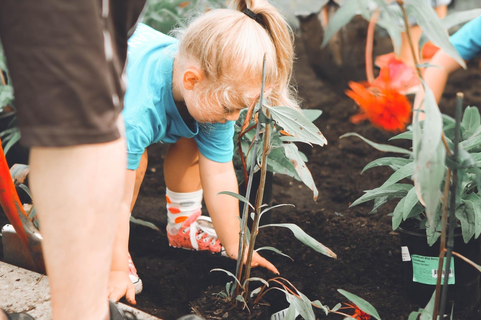 niña plantando en un huerto urbano
